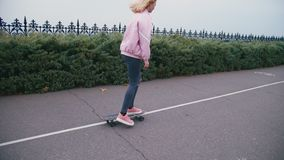 Young pretty beautiful blond hipster woman in pink windstopper having fun riding skateboard longboard downhill on stock footage