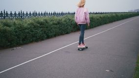 Young pretty beautiful blond hipster woman in pink windstopper having fun riding skateboard longboard downhill on stock video footage