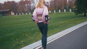 Young pretty beautiful blond hipster woman walking down the road with skateboard longboard in slow motion stock footage