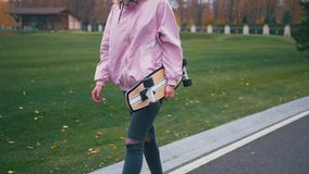 Young pretty beautiful blond hipster woman walking down the road with skateboard longboard in slow motion stock video