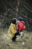 Young pretty beautiful girl in a coat, kisses her young son. On the lips in nature in a coniferous forest, lit from behind by the sun`s rays. Behind it is a Stock Images
