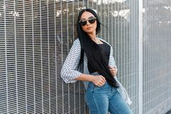 Young pretty beautiful stylish hipster woman with chic long hair in round sunglasses in fashionable clothes stands. Near the modern wall. Urban fashion brunette royalty free stock photo