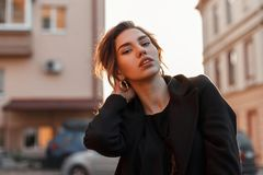 Young pretty beautiful woman in a black stylish t-shirt in a vintage coat with natural make-up with sexy lips near vintage houses royalty free stock photos