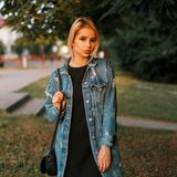 Young pretty beautiful woman in a fashionable denim jacket with a leather handbag in a stylish dress posing outdoors. On a summer day. Glamorous pretty girl stock photo