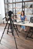 Young pretty blogger recording video on camera. Modern occupation, woman telling about makeup cosmetics in her vlog Stock Photography
