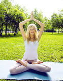 Young pretty blond girl doing yoga in green sunny park at morning, lifestyle sport people concept Stock Images