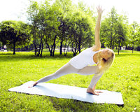 Young pretty blond girl doing yoga in green sunny park at morning, lifestyle sport people concept Royalty Free Stock Images