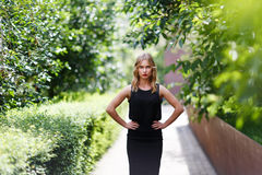 Young pretty blond girl in half growth with hands akimbo royalty free stock photos