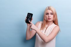 The girl regretfully points at the broken screen of the phone in her hand a blue background. A young, pretty blond girl in a white sweater. With regret, she stock photos