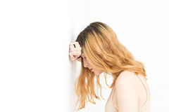 Young pretty blond looking down with her arm on the wall and hea Royalty Free Stock Photography