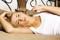 Young pretty blond real woman in bed covered white sheets smilin Royalty Free Stock Photography