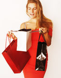 Young pretty blond woman with bags on Christmas sale in red dres. S isolated white background smiling close up Stock Photos