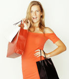 Young pretty blond woman with bags on Christmas. Sale in red dress isolated white background Stock Photo