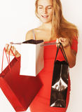 Young pretty blond woman with bags on Christmas. Sale in red dress isolated white background smiling girl cool Stock Image