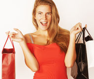 Young pretty blond woman with bags on Christmas. Sale in red dress isolated white background smiling girl cool Stock Photography
