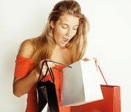 Young pretty blond woman with bags on Christmas. Sale in red dress isolated white close up Royalty Free Stock Photography
