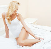 Young pretty blond woman in bed covered white sheets smiling cheerful sexy look close up Royalty Free Stock Photos