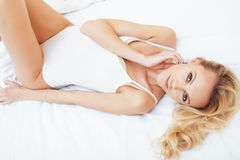 Young pretty blond woman in bed covered white sheets smiling cheerful sexy look close up, happy morning Royalty Free Stock Image