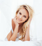 Young pretty blond woman in bed covered white sheets smiling cheerful sexy look close up Stock Image