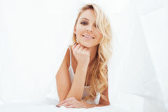Young pretty blond woman in bed covered white sheets smiling cheerful sexy look close up Stock Photo