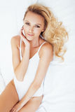 Young pretty blond woman in bed covered white sheets smiling cheerful sexy look close up, happy morning concept Stock Image