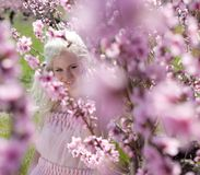 Young pretty blond woman in blooming garden Stock Images