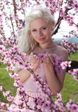 Young pretty blond woman in blooming garden Royalty Free Stock Photography