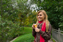 Young pretty blond woman blowing soap bubbles in park Stock Photos