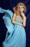 Young pretty blond woman in blue luxury dress Royalty Free Stock Photo