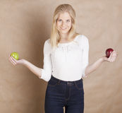 Young pretty blond woman choosing between red and Royalty Free Stock Photos