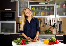Young pretty blond woman cooking fish in kitchen Stock Photos