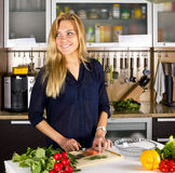 Young pretty blond woman cooking fish in kitchen Stock Photography