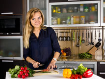 Young pretty blond woman cooking fish in kitchen Royalty Free Stock Photo