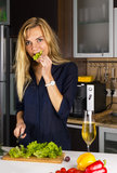 Young pretty blond woman cooking salad in kitchen Royalty Free Stock Photos