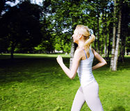 Young pretty blond woman doing sport in park in sunny day at summer, lifestyle people concept Stock Photos