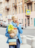 Young pretty blond woman with food in bag walking Royalty Free Stock Photo