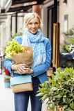 Young pretty blond woman with food in bag walking Stock Photos