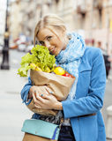 Young pretty blond woman with food in bag walking Stock Images
