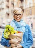 Young pretty blond woman with food in bag walking Royalty Free Stock Photography