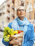 Young pretty blond woman with food in bag walking Stock Photography