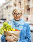 Young pretty blond woman with food in bag walking Royalty Free Stock Images