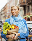 Young pretty blond woman with food in bag walking on street Royalty Free Stock Photos