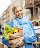 Young pretty blond woman with food in bag walking on street Royalty Free Stock Images