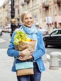 Young pretty blond woman with food in bag walking on street Royalty Free Stock Photography