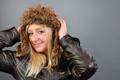 Young, pretty, blond woman in fur cap looks into the camera. Young, pretty, blond woman in a fur cap looks into the camera Royalty Free Stock Photos