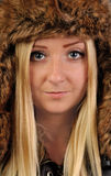 Young, pretty, blond woman in fur cap looks into the camera. Stock Photos