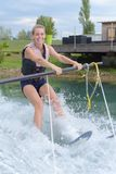 Young pretty blond woman learning to ride wakeboard. Young pretty blond woman learning to ride a wakeboard Stock Images