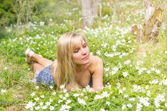 Young pretty blond woman meadow spring flowers. Young pretty blonde woman on a meadow with spring flowers Royalty Free Stock Photo