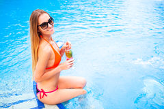 Young pretty blond woman in a orange bikini and sunglasses enjoy Stock Photo