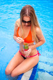 Young pretty blond woman in a orange bikini and sunglasses enjoy Royalty Free Stock Photography